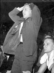 KU coach Dick Harp rises from the bench. During a game in 1958, Harp implored KU fans to stop booing Missouri's Mike Kirksey.