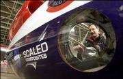 Viewed through one of the plane's portholes, flight engineer Philip Grassa works in the cockpit of the GlobalFlyer in a hanger at the Salina Municipal Airport in Salina Monday.