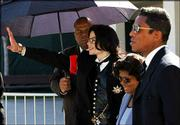 Michael Jackson acknowledges fans as he walks out of court with his mother Catherine and brother Jermaine following the opening day of his child molestation trial at Santa Barbara County Superior court Monday in Santa Maria, Calif.