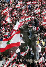 Protesters wave Lebanese flags at the Martyr's Monument in Beirut, Lebanon. In a show of mass support for the opposition in Monday's parliamentary debate, about 25,000 people defied a protest ban and demonstrated calling for Syria to withdraw its army.