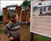 Michelle Dalva, director of Habitat for Humanity's Global Village in Americus, Ga., looks over a sign announcing a Sri Lankan home under construction Monday. Habitat plans to build 25,000 houses, some similar to the one pictured, for victims of the Indian Ocean tsunami. The group will focus on hard-hit Sri Lanka, Thailand, Indonesia and India.