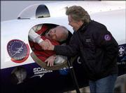 Pilot Steve Fossett shakes hands with Sir Richard Branson as he prepares to take off in the GlobalFlyer at the Salina Municipal Airport. Fossett embarked Monday on an attempt to fly the GlobalFlyer around the world nonstop without refueling. Branson, head of Virgin Atlantic, is financing the mission.