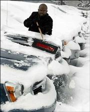 Ernest Bolden, a sales consultant at Meade Dodge in Detroit, clears snow off a Dodge Durango on the sales lot Tuesday. General Motors Corp. and Ford Motor Co. reported sales declines in February, while the smallest of Detroit's Big Three, DaimlerChrysler AG's Chrysler Group, announced sales gains.