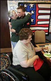 Delores Hopson, left, hugs Marine John Thoennes as Ronnie Lana, foreground, enjoys cake and punch during a welcome-home party for Thoennes. Residents at Pioneer Ridge, 4851 Harvard, who sent Thoennes goodwill packages during his year in Iraq, visited with the Eudora Marine on Thursday.
