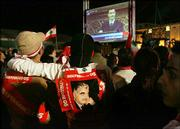 Lebanese opposition protesters, one wearing a picture of slain former Prime Minister Rafik Hariri, watch a live broadcast of Syrian President Bashar Assad's speech on a giant screen set up in the Martyrs Square in Beirut, Lebanon, Saturday.