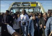 The Rev. Jessie Jackson, far left, walks with marchers Sunday on the Edmund Pettus Bridge in Selma, Ala.. At far right are the Rev. Joseph Lowery and his wife, Evelyn Lowery. Joseph Lowery joined the Rev. Martin Luther King Jr. on the march 40 years ago.
