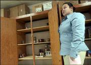 Renee Low, emergency assistance program director with the Lawrence Salvation Army, displays the agency's low stock of food supplies. Area food pantries are running low on supplies such as peanut butter, canned meats and cereal.