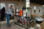 Andy Booth, vice president of the Lawrence Brewers Guild, cleans his homemade brewery, made of kettles, hoses and propane burners.