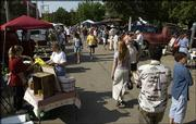 Shoppers peruse the Lawrence Farmers Market for fresh produce and homemade goodies in this 2004 file photo. Market organizers want to move it from 10th and Vermont streets to New Hampshire Street to provide more parking and more vendor space.