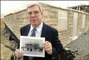 Henry Sweets, curator of the Mark Twain Museum in Hannibal, Mo., stands in front of the new Huck Finn House as he holds a photo of the original home, which was destroyed in 1911. Huck Finn was made famous in novels by Mark Twain.