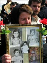 An Iraqi woman holds pictures of victims in this March 16, 2004, file photo at the Halabja memorial hall in Halabja, Iraq, dedicated to the anniversary of the gassing of 5,000 Kurds in the town by Saddam Hussein's regime in 1988.