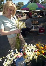 Lora Stoppel, Lawrence, picks out some tuberosas to buy last summer at the Lawrence Farmers Market. A workshop for new and veteran vendors at the market is planned for Saturday at the Douglas County Fairgrounds.
