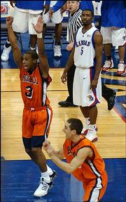 As a dejected Keith Langford (5) looks on, Bucknell's Charles Lee (3) and Kevin Bettencourt celebrate the Bison's 64-63 victory over Kansas University. Bucknell stunned the Jayhawks on Friday in Oklahoma City.