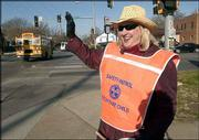 Susan Simmons, a Kansas University graduate who's married with four grown children and one teenager, began working in November as a part-time crossing guard. Waving at passersby as she guards the crossing at 19th and Massachusetts streets, Simmons presents a friendly face for motorists.