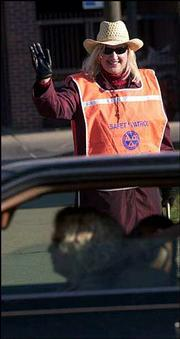 Susan Simmons waves at passers-by as she guards the crossing at 19th and Massachusetts streets.