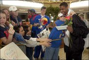 Ruth Ann Schoonover, Topeka, hugs Aaron Miles and gives him roses as the Kansas University men's basketball team arrives at Topeka's Forbes Field Saturday to a crowd of approximately 150 fans. The Jayhawks were knocked out of the NCAA Tournament Friday when Bucknell beat them 64-63.