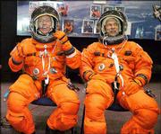 Astronauts Michael Fossum, left, and Piers Sellers wear training versions of their launch and entry suits in the space vehicle mockup facility at Johnson Space Center in Houston. Fossum and Sellers, who are on the crew for the next Atlantis mission, also would fly on a rescue mission to bring back the Discovery astronauts if that shuttle were damaged during flight.