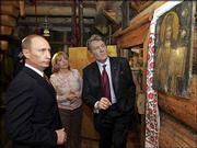 Russian President Vladimir Putin, left, examines part of a collection of antiques at the country home of Ukrainian President Viktor Yushchenko, right, and his wife, Kateryna. Yushchenko on Saturday pledged to build stronger ties between their neighboring states as the Kremlin leader made his first visit to Kiev since the pro-Western government took power.