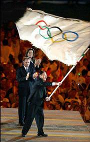 Wang Qishan, mayor of Beijing, which will play host to the 2008 Olympics, receives the Olympic flag Aug. 29 during the closing ceremonies of the 2004 Olympic Games in Athens, Greece. China is becoming a bigger player on the world stage -- economically, politically and athletically.