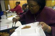 Sonya Johnson, foreground, Lawrence, NAACP branch president, serves during the annual soul food dinner on Saturday at First Baptist Church, 1330 Kasold Drive. Ruby Johnson, center, and Donna Bell, Lawrence NAACP branch vice president, both of Lawrence, also participated.