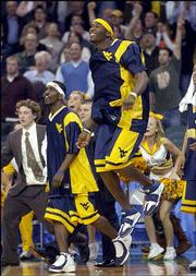 Players on the West Virginia bench erupt as the Mountaineers beat Wake Forest, 111-105 in double overtime. West Virginia won the thriller Saturday in Cleveland.