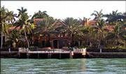 Palm trees surround a waterfront mansion on Star Island, as seen from an Island Queen Cruise tour of Miami's Millionaires Row, home to the rich and famous.