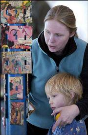 Cary Allen and her son Sam, 6, Lawrence, look at decorated switchplates at the annual YART sale, an East Lawrence neighborhood-wide yard sale that featured arts, crafts and live music. The switchplates were made by artist Stacey Van Houten, who participated in the sale Saturday inside New York School's gymnasium.