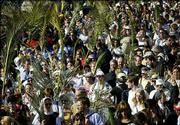Christian pilgrims walk down the Mount of Olives in Jerusalem, some holding palm leaves, during the traditional Palm Sunday procession. Palm Sunday, which begins Christianity's most solemn period, marks Jesus' entrance into Jerusalem, when his followers laid palm branches in his path.