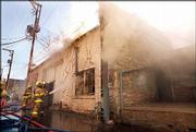Lawrence Firefighters battle a fire in a storage building owned by Weaver's Department Store in this April 2000 file photo. City and fire officials say that more extensive use of sprinkler systems could prevent the spread of fire downtown.