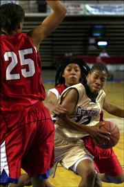 Central Arizona's Shaquina Mosley drives past Moberly Area College's Meshaq Williams (25) and Ashley Lovelady during the NJCAA Women's National Championship tournament Tuesday at the Bicentennial Center in Salina. Mosley, a Kansas University signee, was named junior-college player of the year Wednesday.