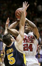 Texas Tech guard Ronald Ross (24) shoots over West Virginia guard Johannes Herber. The Red Raiders lost, 65-60, Thursday in Albuquerque, N.M.