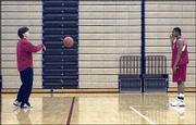 First-year Kansas University women's basketball coach Bonnie Henrickson, left, rebounds the ball for junior forward Crystal Kemp after a Dec. 4 practice at Horesji Center.