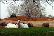 Workers continue installing berms between the driving range and Alvamar Public golf course Monday. The facility, which also replaced its greens last fall, hopes to reopen in April.