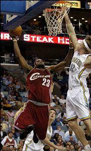 Cleveland's LeBron James (23) goes to the basket around New Orleans' Chris Andersen in the second half of the Cavaliers' 109-108 overtime victory. James scored 44 in Cavs' victory Monday in New Orleans.
