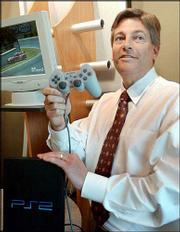 Victor Viegas, Immersion chief executive, demonstrates a Sony Corp. PlayStation2 game controller Monday at Immersion headquarters in San Jose, Calif. Sony Corp. has been ordered to pay $90.7 million and halt U.S. sales of PlayStation consoles for infringing on the patents of Immersion, which develops and licenses touch-feedback technology to enhance video game realism.