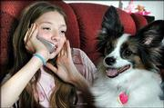 Patty Wiegner sits with her dog Bingo at her Valrico, Fla., home talking with a friend. Patty, 11, wanted just two things for Christmas -- a cellular phone and a dog. She got both of her wishes.