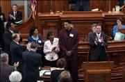 KU basketball senior Wayne Simien, center, is given a standing ovation in the House of Representatives at the Topeka Statehouse Wednesday for being an All-American for the Jayhawks this year. Simien was joined by his family from left, his father and mother Wayne, Sr. and Margaret Simien and his sister Dione Leng. At right is KU men's basketball coach Bill Self. Simien was honored in both chambers at the statehouse and met with Gov. Kathleen Sebelius.