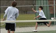 Free State high sophomore Jack Hull, right, chases down a volley during No. 2 doubles against Shawnee Mission South. Hull and his partner, senior Charles Guard, left, lost to the Raiders' Jeff White and Brian Hiller, 8-7 (7-4), Tuesday at FSHS.