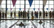 Teammates line the side of the Knox Natatorium as swimmers compete in the 200-yard freestyle at the LHS Invitational. Lawrence High placed second at the three-team meet Tuesday at LHS.