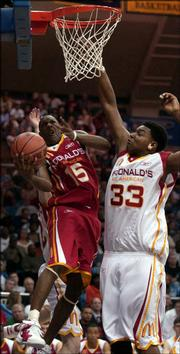 Mario Chalmers, left, makes a circus shot against Andrew Bynum in the second half of the McDonald's All-American game.