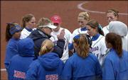 KU softball coach Tracy Bunge, wearing visor, tries to rally the team after it allowed five runs in the fifth inning of a 7-3 loss to Nebraska. The Huskers won Wednesday at Arrocha Ballpark.