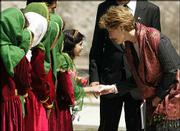 First lady Laura Bush, right, is greeted by Afghan schoolchildren upon her arrival at Kabul University in Afghanistan. Mrs. Bush spent about six hours in the country Wednesday.