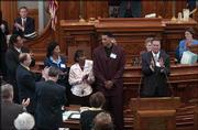 Kansas University basketball senior Wayne Simien, center, is given a standing ovation Wednesday in the Kansas House of Representatives for being an All-American for the Jayhawks this year. Simien was joined by his family, from left, his father, Wayne Sr., and his mother, Margaret Simien, and his sister, Dione Leng. At right is KU men's basketball coach Bill Self. Simien was honored in both chambers at the Statehouse and met with Gov. Kathleen Sebelius.