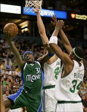 Dallas' Jason Terry, left, drives to the hoop against Boston's Raef LaFrentz, center, and Paul Pierce. The Mavericks defeated the Celtics, 112-100, Wednesday night in Boston.