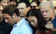 Terri Schiavo's father, Bob Schindler, right, listens to son Bobby Schindler, left, read a statement during a news conference Thursday outside the Woodside Hospice, where Schiavo died earlier in Pinellas Park, Fla. At center is Schiavo's sister, Suzanne Vitadamo.