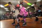 A Bionics jammer, center, designated by a star worn on her helmet, tries to sneak through a pack of Dogfightin' Dames blockers to score points. The Dogfightin' Dames took on The Bionics on March 19 at the Winnwood Skate Center in Kansas City, Mo.