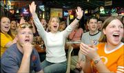 Baylor basketball fans, including Ryan McCormick, front left, and Meghen Rutland, middle, support their Bears. The fans were at a Waco, Texas, restaurant watching Monday's NCAA regional final victory.