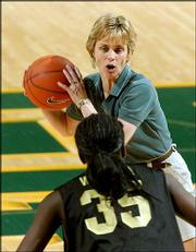 Baylor women's basketball coach Kim Mulkey-Robertson works with forward Abiola Wabara (35) during a practice. The Bears worked out Wednesday in Waco, Texas, in preparation for their trip to the Final Four -- a berth that has given the school a needed lift.