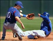 Kansas City's Joe McEwing, right, steals second base as the ball gets away from Texas shortstop Michael Young. The Rangers defeated the Royals, 3-0, Thursday in Surprise, Ariz.