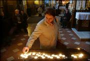 A woman lights a candle as people pray in a church in Wadowice, southern Poland, the Pope's native town. Hundreds of people in Wadowice prayed and kept a hopeful vigil Friday at the 500-year-old church where Karol Wojtyla was baptized, remembering their personal encounters with perhaps the most famous Pole in history.